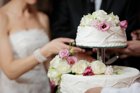 Photo pour A bride and a groom is cutting their wedding cake - image libre de droit