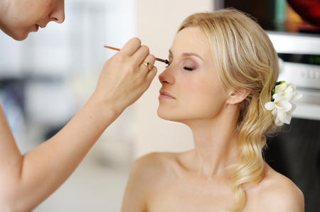 Photo for Young beautiful bride applying wedding make-up  by professional make-up artist - Royalty Free Image