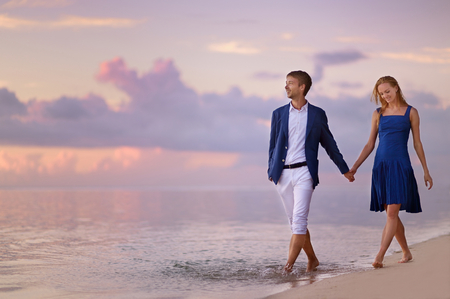 Foto de Beautiful romantic couple on a sunset on tropical beach - Imagen libre de derechos