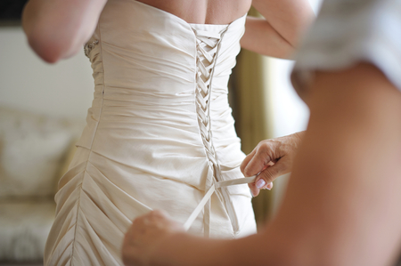 Photo pour Helping the bride to put her wedding dress on - image libre de droit