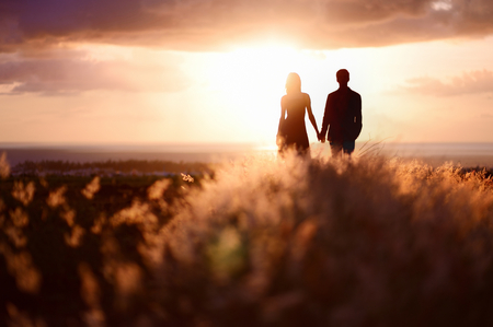 Photo pour Young couple enjoying the sunset in the meadow - image libre de droit