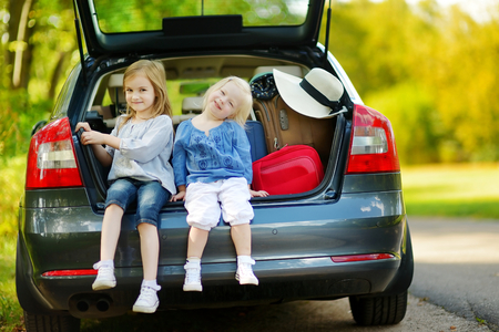 Photo pour Two adorable little sisters sitting in a car just before leaving for a car vacation with their parents - image libre de droit