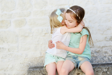 Photo for Two adorable little sisters laughing and hugging each other on warm and sunny summer day in italian town - Royalty Free Image
