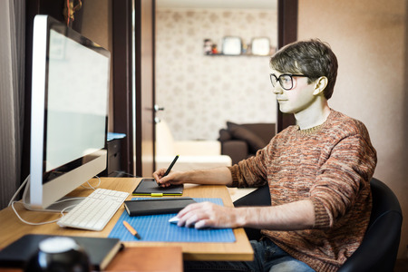 Photo for Young man at home using a computer, freelance developer or designer working at home. - Royalty Free Image