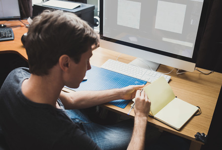 Photo for Young man at home using a computer, freelance developer or designer working at home - Royalty Free Image