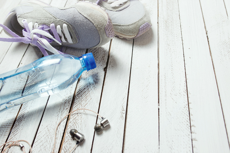 Pair of sport shoes, water bottle and earphones on white wooden background