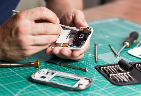 Photo pour Man repairing broken smartphone, close up photo. - image libre de droit