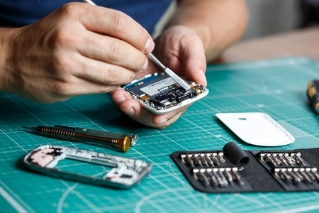 Foto de Electronics repair service. Technician disassembling smartphone for inspecting. - Imagen libre de derechos