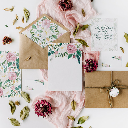 Photo pour Workspace. Wedding invitation cards, craft envelopes, pink and red roses and green leaves on white background. Overhead view. Flat lay, top view - image libre de droit