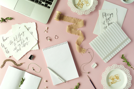 Photo for Flat lay, top view office table desk. feminine desk workspace with laptop, diary, spool with ribbon, calligraphy quotes and golden clips on pink background. - Royalty Free Image