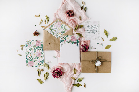 Foto für Workspace. Wedding invitation cards, craft envelopes, pink and red roses and green leaves on white background. Overhead view. Flat lay, top view - Lizenzfreies Bild