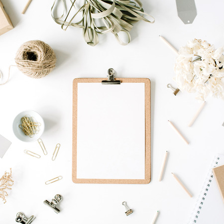 Photo for Flat lay, top view office table desk. feminine desk workspace mock up with clipboard, twine, pencils, floral bouquet, craft diary and clips on white background. - Royalty Free Image