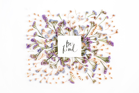 Foto de Words Be Kind written in calligraphic style on paper with blue and purple dried flowers on white background. Flat lay, top view - Imagen libre de derechos