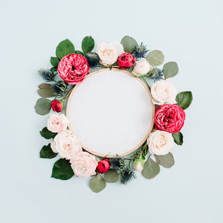 Foto de Embroidery frame with beige rose flower buds isolated on pale pastel blue background. Flat lay, top view decorated concept. - Imagen libre de derechos