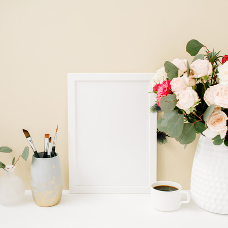 Foto de Home office desk with photo frame mockup, beautiful roses and eucalyptus bouquet in front of pale pastel beige background. Blog, website or social media concept . - Imagen libre de derechos