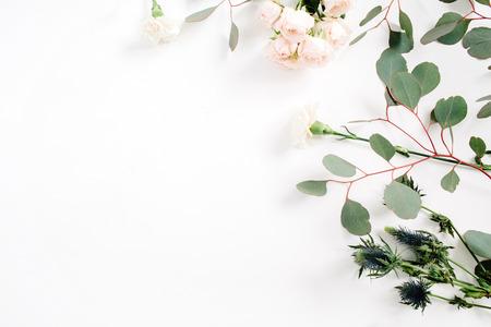 Photo pour Beige rose flowers, eringium flower, eucalyptus branches on white background. Flat lay, top view. Floral background - image libre de droit
