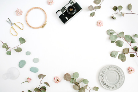Foto de Flat lay border frame with retro camera, eucalyptus branches, plate and scissors on white background. Top view artist background with space for text. - Imagen libre de derechos