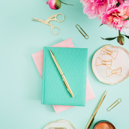 Photo for Flat lay home office desk. Female workspace with pink peony flowers bouquet, golden accessories, pink and mint diary on mint background. Top view feminine background. - Royalty Free Image