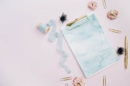 Photo pour Flat lay of clipboard, rose buds, blue ribbon, golden pen and clips on pale pink background. Top view stylish decorated mock up. - image libre de droit