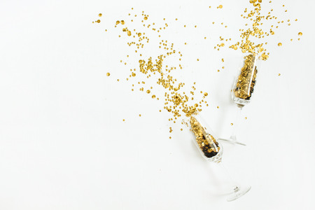 Photo for Glasses with golden confetti tinsel on white background. Flat lay, top view celebrate party concept. - Royalty Free Image