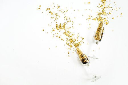 Foto de Champagne glasses with golden confetti tinsel on white background. Flat lay, top view celebrate party concept. - Imagen libre de derechos