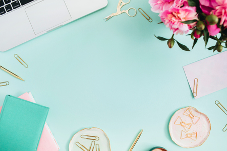 Photo for Flat lay home office desk. Female workspace with laptop, pink peonies bouquet, golden accessories, pink and mint diary on mint background. Top view feminine background. - Royalty Free Image