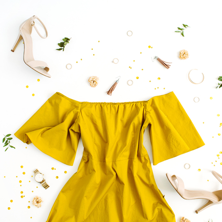 Foto de Women's fashion clothes and accessories on white background. Flat lay female golden styled look with dress, high heels, watch, bracelet. Top view. - Imagen libre de derechos