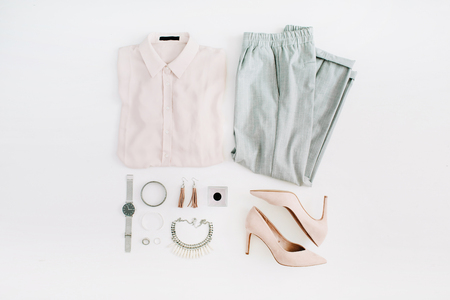 Foto de Women modern fashion clothes and accessories. Flat lay female casual style look with pastel blouse, trousers, high heels, watch, perfume, necklace, earrings. Top view. - Imagen libre de derechos
