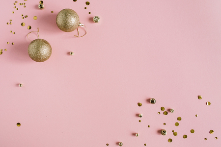 Foto de Golden confetti and Christmas toy balls on pink background. Flat lay, top view holiday background. - Imagen libre de derechos