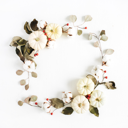 Foto de Wreath frame made of white pumpkins, red berries, cotton balls and eucalyptus branches on white background. Flat lay, top view Christmas composition. - Imagen libre de derechos