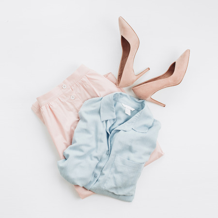 Photo pour Woman pastel clothes: jeans shirt, skirt, high-heel shoes on white background. Flat lay, top view female fashion collage. - image libre de droit
