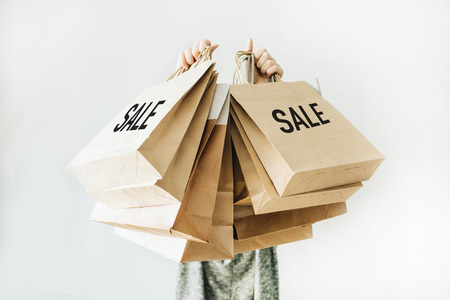 Photo pour Black Friday sales discount concept. Young woman hold craft paper bags with word Sale on white background. - image libre de droit