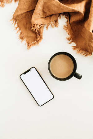 Foto de Mug of coffee with milk, brown blanket, smart phone with blank screen mockup on white background. Flat lay, top view. - Imagen libre de derechos