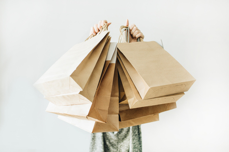 Foto de Black Friday sales discount concept. Young woman hold craft paper bags with word Sale on white background. - Imagen libre de derechos