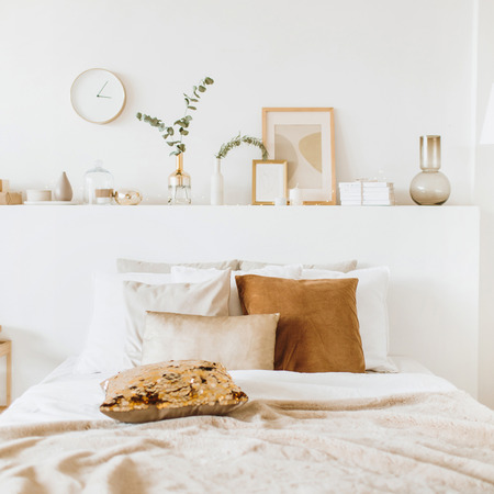 Foto de Modern interior design concept. Bright beige and golden style bedroom with bed, pillows, bedcover, clock, eucalyptus branch, vase, candle. - Imagen libre de derechos