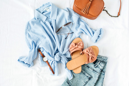 Photo for Feminine summer fashion composition with blouse, slippers, purse, sunglasses, watch, jean shorts on white background. Flat lay, top view minimalist clothes collage. Female fashion blog, social media, website concept. - Royalty Free Image
