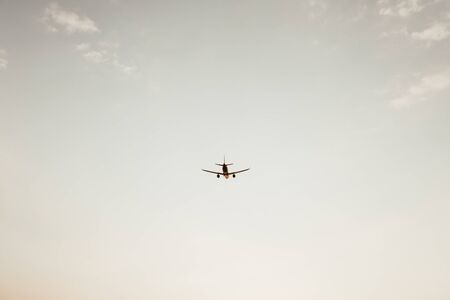 Foto de Airplane flying in the sky at sunset with little clouds. Travel, vacation and holiday concept. Vintage and retro tones filter. Minimalistic background. - Imagen libre de derechos