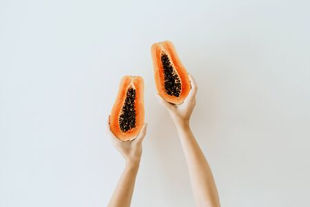 Photo for Summer and travel concept. Young woman's hands holding exotic tropical orange papaya fruit. Minimalistic seasonal vegetarian background. Front view. - Royalty Free Image