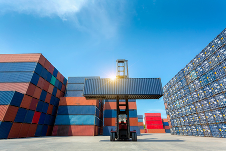 Photo for Forklift truck lifting cargo container in shipping yard or dock yard against blue sky with cargo container stack in background for transportation import,export and logistic industrial concept - Royalty Free Image