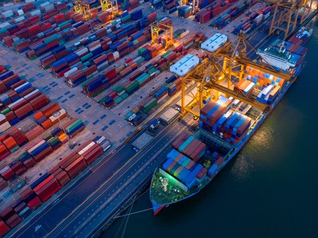 Foto per Aerial view of Containers yard in port congestion with ship vessels are loading and discharging operations of the transportation in international port.Shot from drone. - Immagine Royalty Free