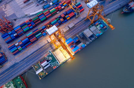 Foto per Aerial view of business port with shore crane loading container in container ship in import/export and business logistics with crane and shipping port cargo.International transportation and port concept. - Immagine Royalty Free