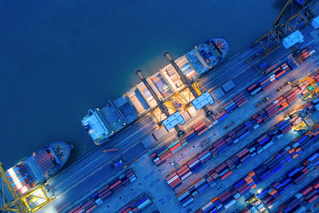 Foto per Aerial view of business port with shore crane loading container in container ship in import/export and business logistics with crane and shipping port .International transportation and port concept. - Immagine Royalty Free