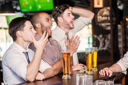 Photo for Men fans watching football on TV and drink beer. Three other men drinking beer and having fun together in the bar until the bartender communicates with them - Royalty Free Image