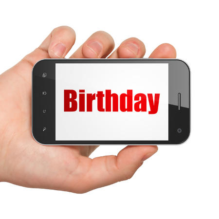 Holiday concept: Hand Holding Smartphone with  red text Birthday on display