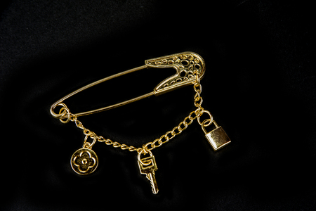 Foto de Decorative safety pin with chain on black - Imagen libre de derechos