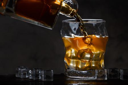 Foto de Whiskey bottle flowing into a glass of ice on a dark background - Imagen libre de derechos