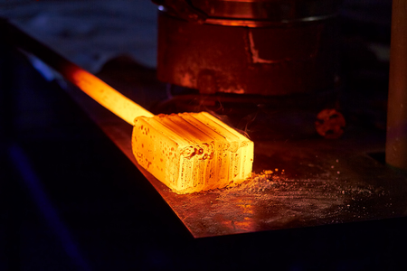 Photo for Glowing iron ingot on the table. Hot metal workpiece for the manufacture of Damascus steel. - Royalty Free Image