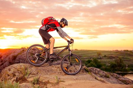Foto de Cyclist Riding the Bike Down Hill on the Mountain Rocky Trail at Sunset. Extreme Sports - Imagen libre de derechos