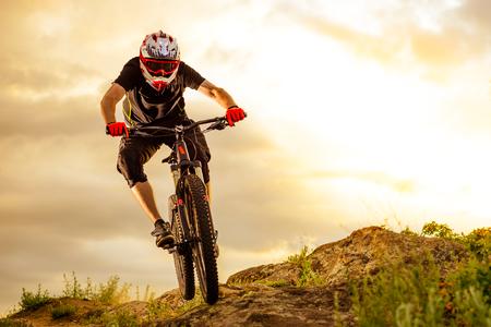 Photo pour Professional Cyclist Riding the Bike Down Rocky Hill at Sunset. Extreme Sport Concept. Space for Text. - image libre de droit
