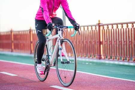 Foto de Young Woman in Pink Jacket Riding Road Bicycle on the Bridge Bike Line in the Cold Sunny Autumn Day. Healthy Lifestyle. - Imagen libre de derechos